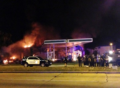 Authorities respond near a burning gas station as dozens of people protest following the fatal shooting of a man in Milwaukee