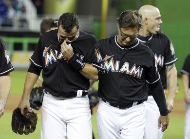 Martin Prado is consoled by Miami Marlins team manager Don Mattingly.