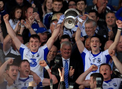 Waterford players Patrick Curran and Adam Farrell lift the trophy.