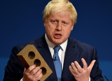 Boris Johnson holds a brick during a 2014 speech