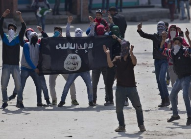 Muslim protesters hold a flag of Islamic State as they shout anti-India slogans during a protest in Srinagar, Indian controlled Kashmir.