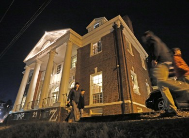 Students walk by the Phi Kappa Psi house at the University of Virginia.