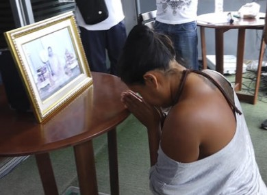 Umaporn Sarasat, 43, pays respects in front of a portrait of Thailand's King Bhumibol Adulyadej in Ko Samui, Thailand.