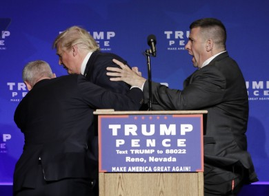 Members of the Secret Service rush Republican presidential candidate Donald Trump off the stage at a campaign rally in Reno, Nevada yesterday.
