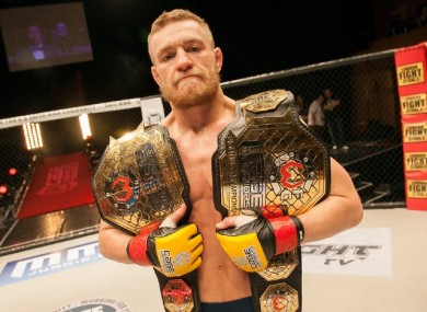 Conor McGregor with the Cage Warriors featherweight and lightweight belts after defeating Ivan Buchinger at The Helix in December 2012.