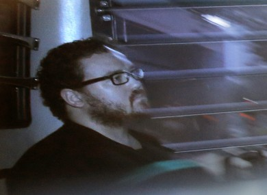 In this file photo taken through tinted glass, Rurik Jutting, a British banker, sits in a prison bus as he arrives at a court in Hong Kong.