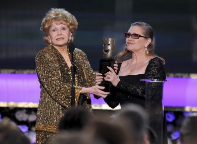 Carrie Fisher, right, presents her mother Debbie Reynolds with the Screen Actors Guild life achievement award at the 21st annual Screen Actors Guild Awards at the Shrine Auditorium in Los Angeles last year.
