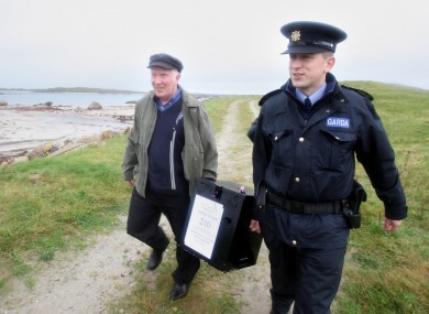 Electoral officer, Hugh O'Donnell with Garda Brendan McCann, carry the ballot box, for the Lisbon Treaty voting, on Inishfree Island off the coast of Co Donegal.