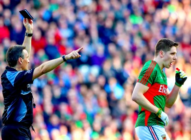 Referee Maurice Deegan shows Lee Keegan a black card.