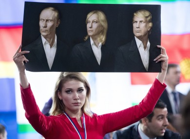 The holy trinity: A Russian journalist holds up portraits of Vladimir Putin, Marine Le Pen of France, and US president-elect Donald Trump in Moscow today.
