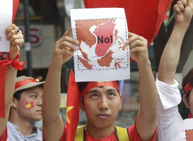 A Vietnamese protester showing a map marked