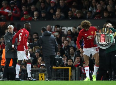 Jose Mourinho pats Manchester United's Paul Pogba on the back after the player is forced to leave the pitch with an injury.