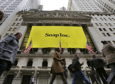 People pass by the New York Stock Exchange after the banner for the Snap Inc. IPO was raised on the building's facade.