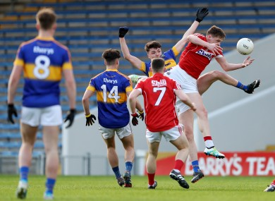Tipp's Conall Kennedy competes for possession with Cork's Jack Murphy .