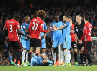 Aguero lies on the ground as Fellaini is shown red.