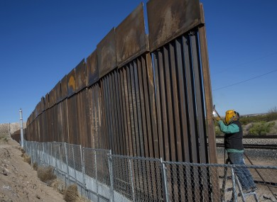 A worker welds a new fence between the Anapra neighborhood of Ciudad Juarez, Mexico and Sunland Park, New Mexico,