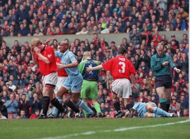 Coventry City's David Busst (r) lies in agony on the turf after breaking his leg as teammate Dion Dublin (second l) yells for a stretcher and Manchester United's David May (l), Peter Schmeichel (c) and Denis Irwin (second r) turn away, horrified during a Premier League match on 8 April 1996.