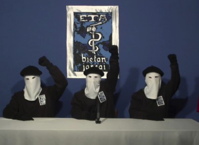 File: Masked members of the Basque separatist group ETA raise their fists in unison following a news conference at an unknown location.