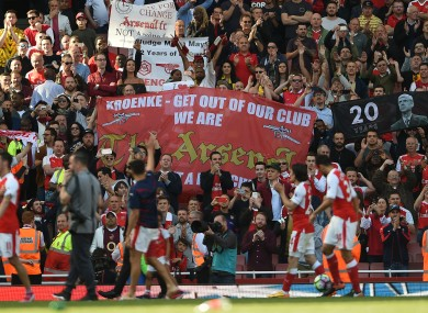 Arsenal fans hold various banners as the players complete a lap of appreciation.