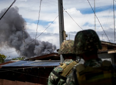Philippine marines look at smoke following an airstrikes by Philippine Air Force in Marawi.
