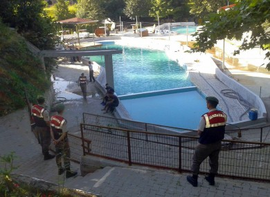 Paramilitary police officers investigate after five people were caught up in an electrical current in the pool at the park in the town of Akyazi, in Sakarya province, western Turkey.