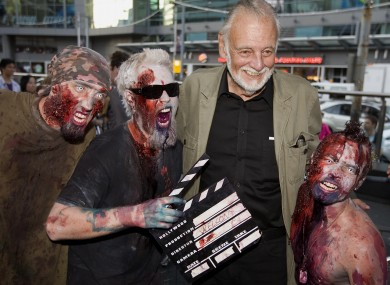 George Romero poses with some fans dressed as zombies after accepting a special award during the 2009 Toronto International Film Festival in Toronto.