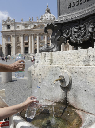 Tourists fill their bottles at the drinking fountain next to St Peter's square at the Vatican.