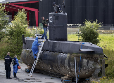 Police technicians board the amateur -built submarine UC3 Nautilus on a pier in Copenhagen harbour, Denmark.