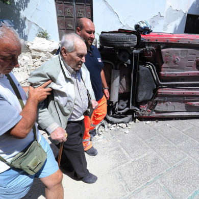 A man is helped to walk past an overturned car and a damaged house in Casamiccioloa, Italy.