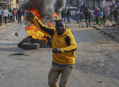 A man throws a stone towards police in Kibera, Nairobi, Kenya, as people block roads with stones to protest in support of Kenyan opposition leader and presidential candidate Raila Odinga.