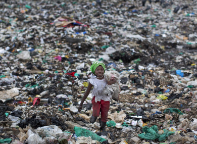 File photo of a young girl holding the plastic bottles she has scavenged, as she walks amidst garbage and plastic bags at the garbage dump in the Dandora slum of Nairobi, Kenya.