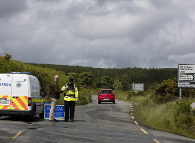 A garda stands near the crime scene where the body parts were found in the Wicklow Mountains