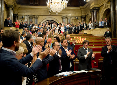 Pro-independence members of the Catalan parliament celebrate after last night's meeting.