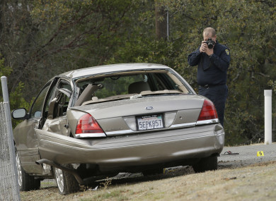 A California Highway patrol officer photographs a vehicle involved in a deadly shooting rampage at the Rancho Tehama Reserve