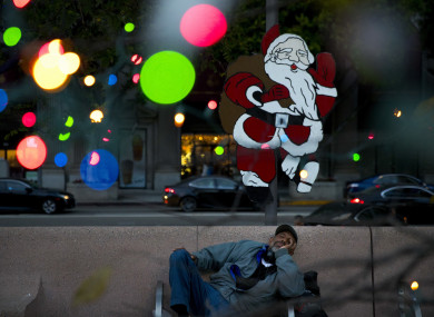 Homeless man Alonzo Harrison, 47, takes a nap on a bench at Pershing Square decorated with Christmas lights in the background in LA.