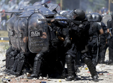A police officer fires rubber bullets at demonstrators during a general strike against a pension reform measure in Buenos Aires, Argentina, earlier this month.