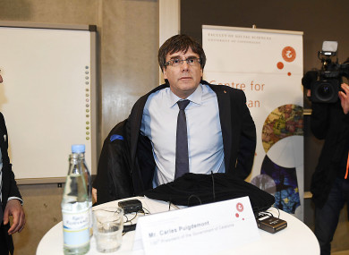 Carles Puigdemont takes off his coat as he prepares to take part in the debate at the University of Copenhagen.