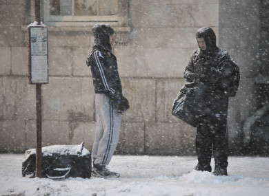 File photo of people waiting for a bus in the snow