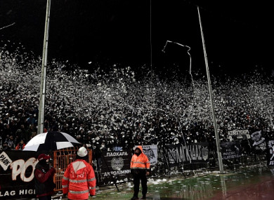 Paok's supporters throw toilet rolls and other projectiles prior to the Greek Superleague match against Olympiakos.