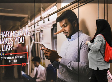 A commuter walks past an advertisement reading 'sharing a lie makes u a liar' at a train station in downtown Kuala Lumpur.