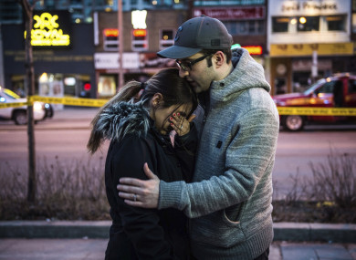 A man consoles his wife at the scene