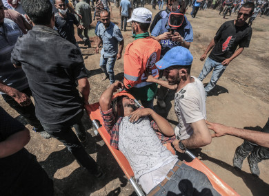 Palestinians evacuate an injured man during clashes with Israeli Security Forces along the Israel-Gaza border
