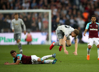 Manchester United's Scott McTominay (centre) and West Ham United's Aaron Cresswell battle for the ball .