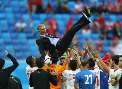 Iran's players celebrate their win over Morocco with coach Carlos Queiroz