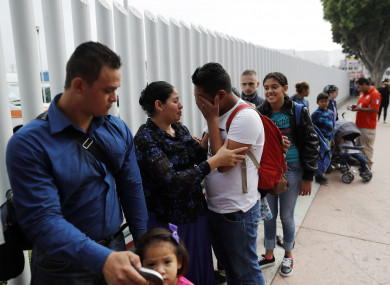 Calet Garcia, center in white shirt, of Honduras, cries once he realizes he will be able to apply for asylum in the U.S. with his friend Daisy Avelar, second from left, of El Salvador, Thursday, July 26, 2018, near the San Ysidro port of entry in Tijuana, Mexico