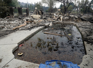 Debris and charred items litter a wildfire-ravaged home