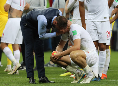 England's head coach Gareth Southgate (L) comforts Harry Maguire.