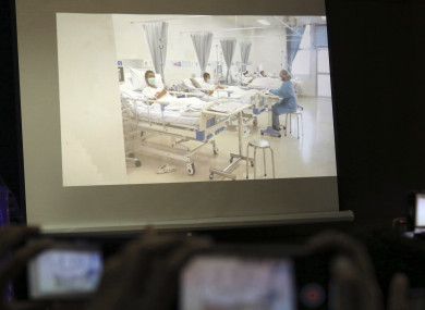Members of the media try to photograph a projected image of the rescued boys in their hospital room during a police press conference in Chiang Rai province, northern Thailand.