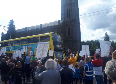 A bus and the march pass the church in the Chapelizod.