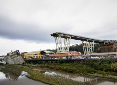 A picture taken on Tuesday shows vehicles standing on a part of a Morandi motorway bridge after a section collapsed earlier in Genoa